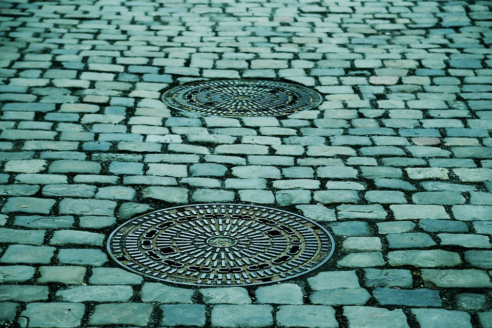 a cobbled road with manhole-covers